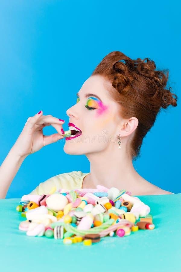 有甜好吃的东西和糖果的女孩 库存图片
