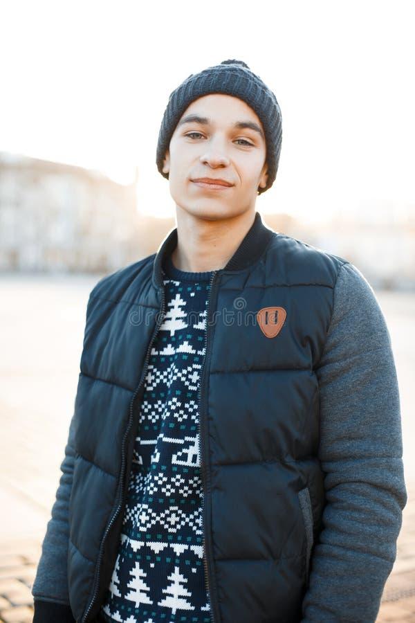 有甜微笑的英俊的年轻人在圣诞节被编织的毛线衣的葡萄酒时髦的帽子在一件时兴的夹克 库存照片