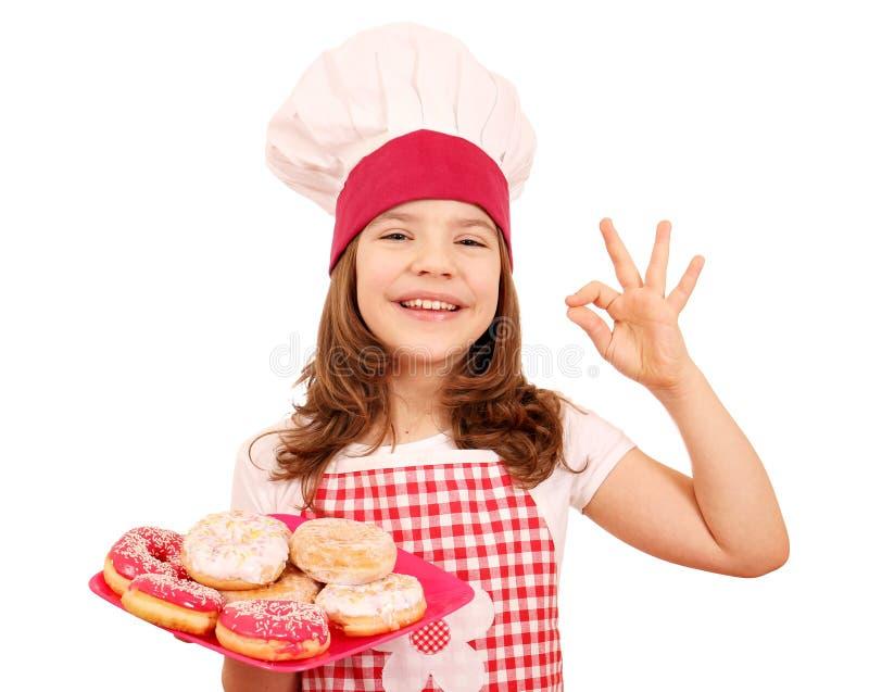 有甜油炸圈饼的小女孩厨师和好手签字 免版税库存图片