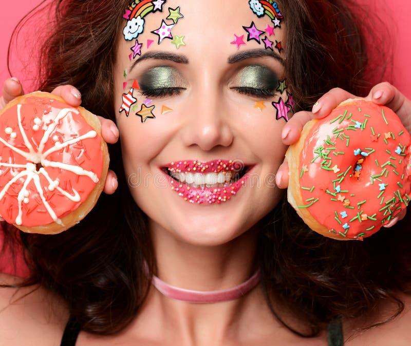 有甜点五颜六色的油炸圈饼的秀丽时髦的时装模特儿女孩 库存照片