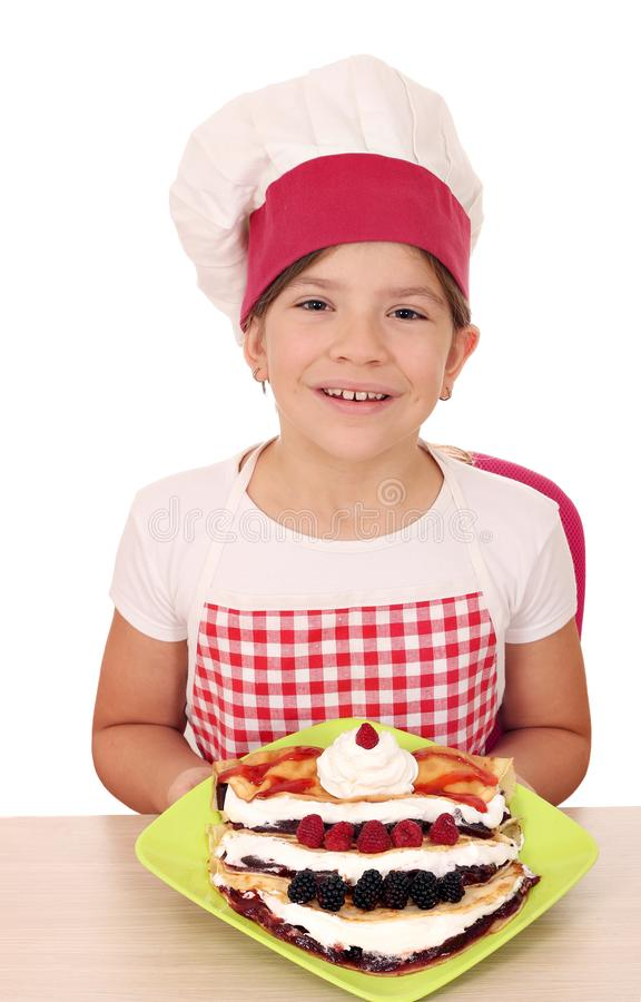 有甜绉纱和果子的女孩厨师 免版税库存图片