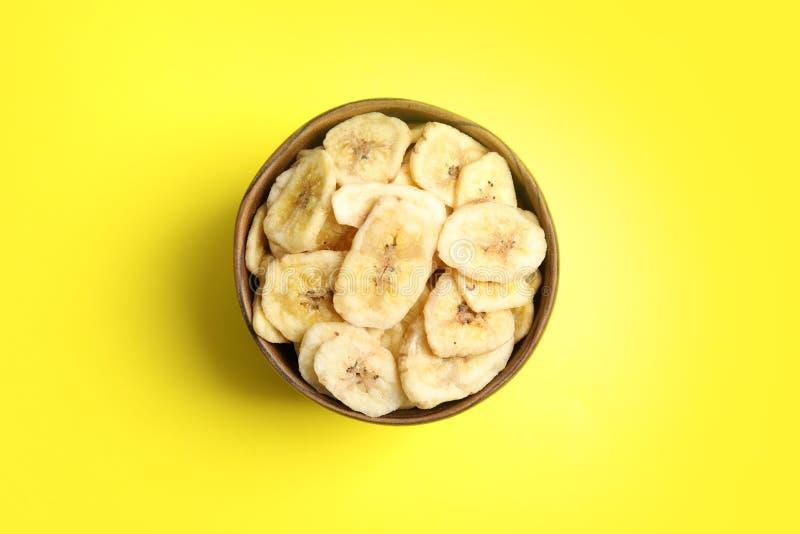 有甜香蕉切片的木碗在颜色背景,顶视图 3个接近的干果类型 免版税库存图片