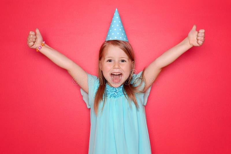 有生日帽子陈列赞许姿态的逗人喜爱的女孩在颜色背景 免版税库存照片