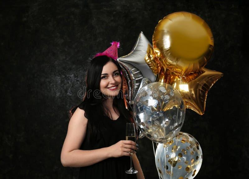 有生日气球和杯的年轻女人在黑暗的背景的香槟 图库摄影
