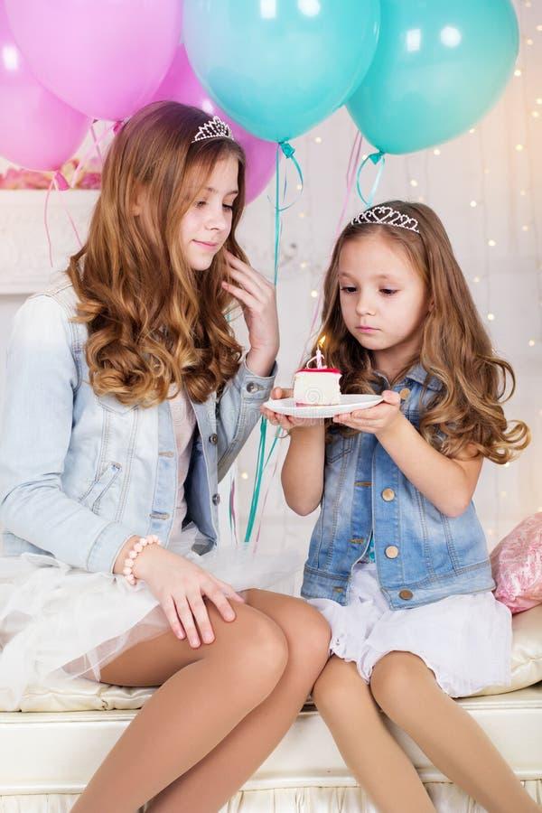 有生日蛋糕和气球的两个俏丽的女孩 库存照片