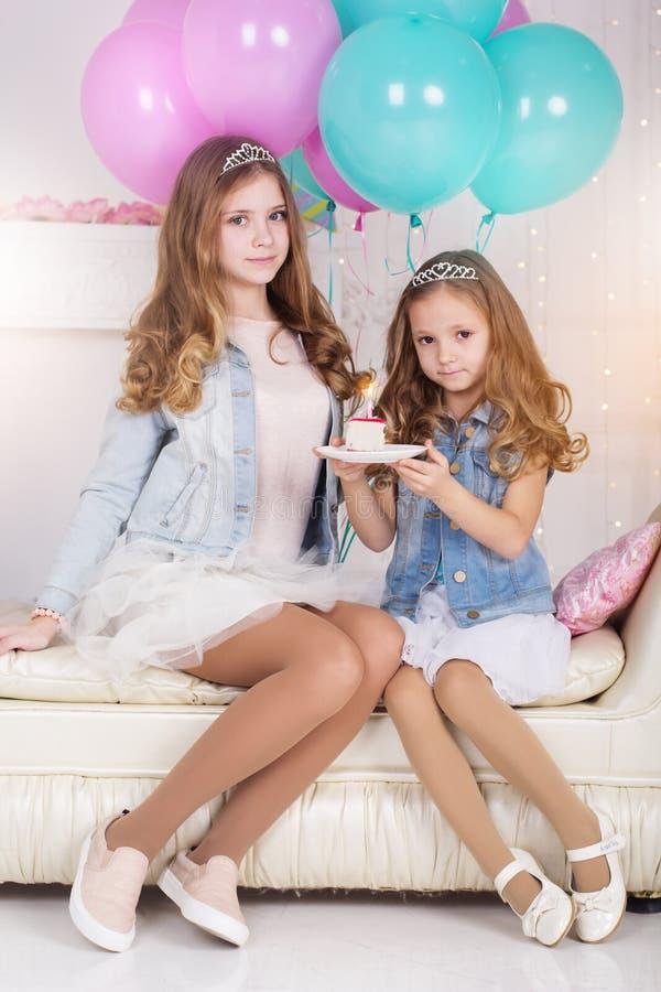 有生日蛋糕和气球的两个逗人喜爱的女孩 免版税库存照片