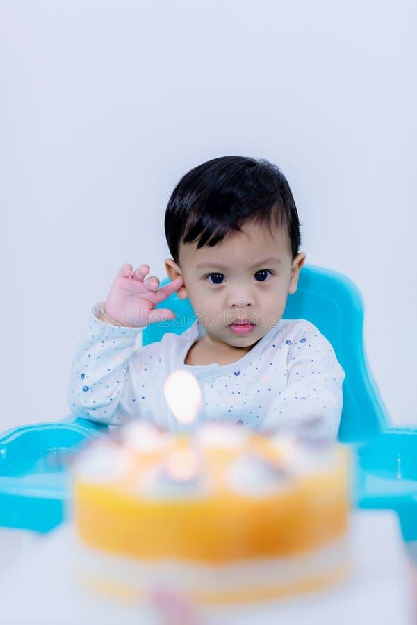 有生日蛋糕的逗人喜爱的小男孩坐椅子在屋子里 库存照片