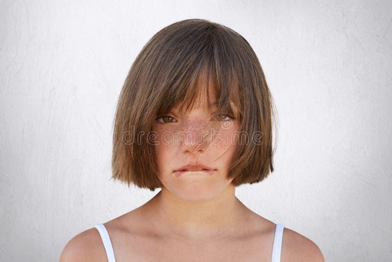 有生气的小女孩与她的父母的争吵,看无辜地入照相机,当弯曲她的嘴唇被隔绝在白色backg时 库存图片
