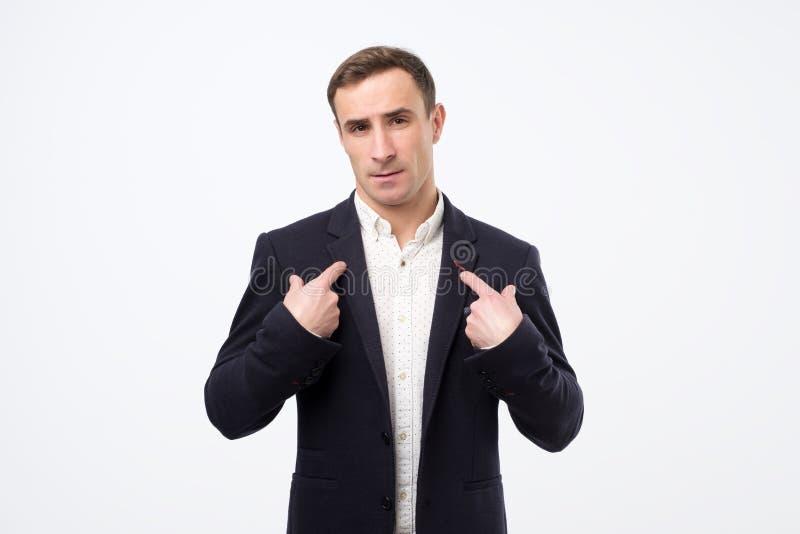 有生气询问的面孔的英俊的年轻白种人人把手指指向的他自己 库存照片