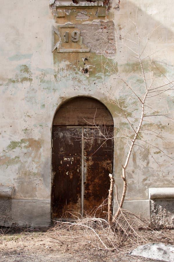 有生锈的金属门的葡萄酒破旧的房子墙壁关闭了 垂直的视图 免版税库存照片