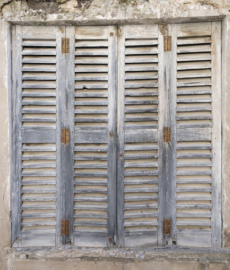 有生锈的铰链的老脏的灰色快门在残破的墙壁 图库摄影