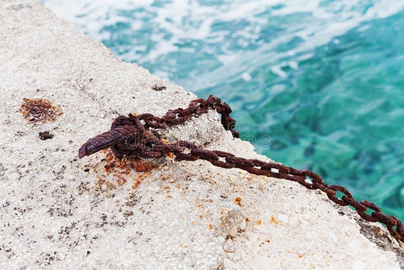 有生锈的链子的老勾子在具体海码头登上了 渔船和小船的停泊设备 免版税库存图片