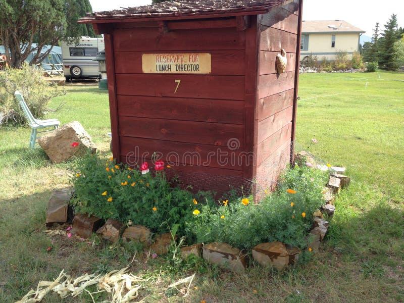 有生长在它附近的野花的外屋 库存图片
