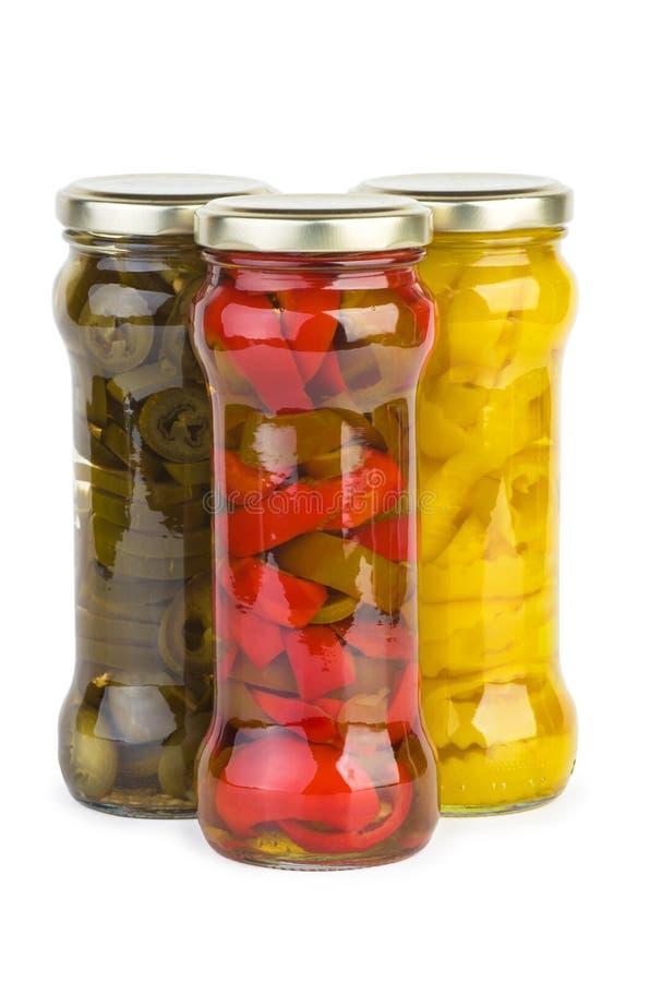 有用卤汁泡的红色,黄色和青椒切片的玻璃瓶子 免版税库存照片