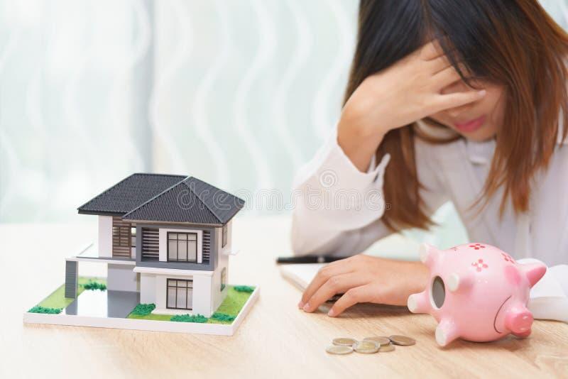 有用尽的金钱被注重的妇女在存钱罐和她的h 库存图片