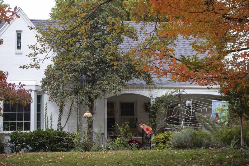 有用巨大的蜘蛛网装饰的长得太大的围场和秋叶的俏丽的白色房子和装饰旗子为万圣节-框架 免版税库存图片