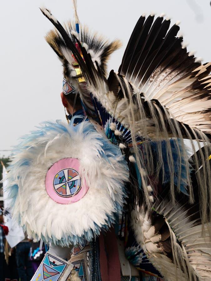 有用羽毛装饰的头饰的美国本地人花梢舞蹈家和熙来攘往和羽毛和串珠的大奖章胳膊盾 免版税图库摄影