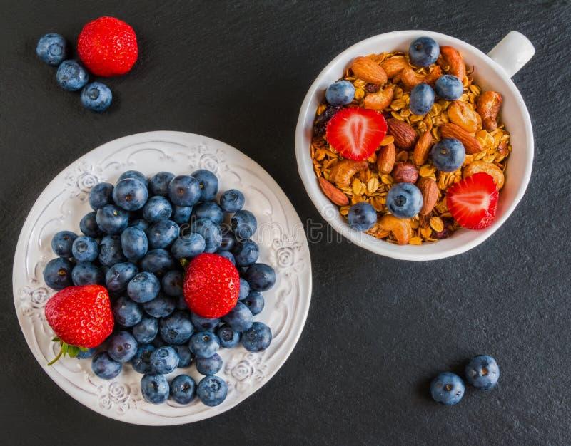 有由燕麦剥落做的格兰诺拉麦片的早餐碗、干果子和坚果和新鲜的蓝莓和草莓 免版税图库摄影