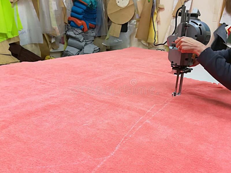 有电刀子的裁缝削减了缝合的出口零件 免版税库存照片