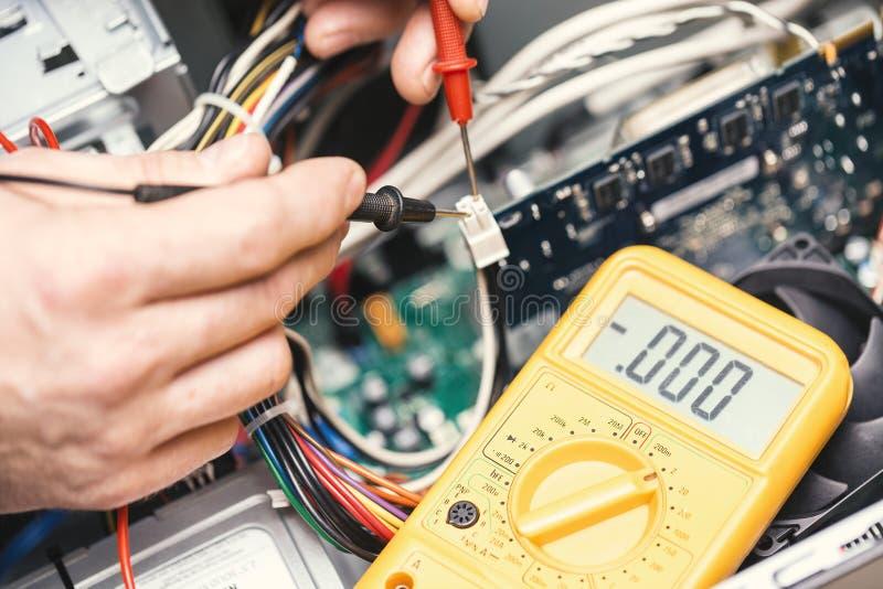 有电压表的技术员手在计算机主板上 计算机概念修理  定调子与选择聚焦 库存图片