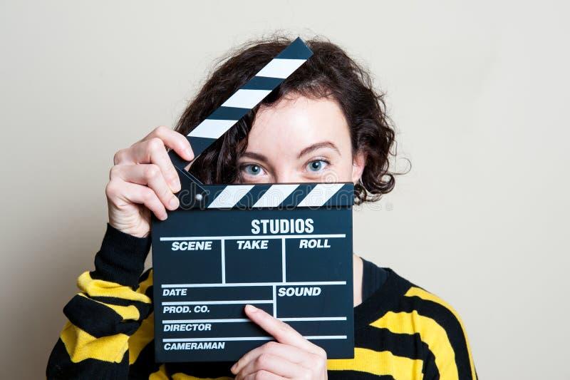 有电影拍板的微笑的女孩在白色背景 库存图片