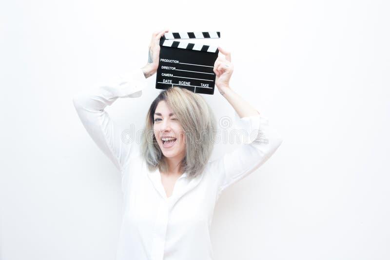 有电影拍板的年轻蓝眼睛白肤金发的妇女 图库摄影