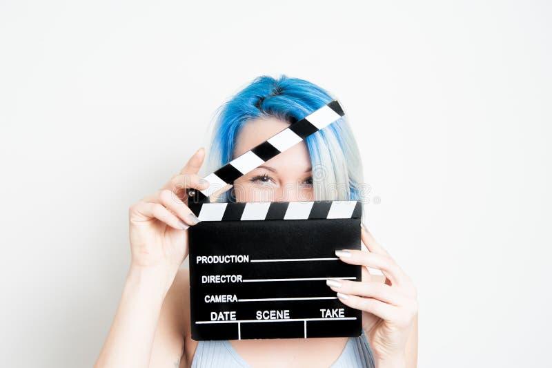 有电影拍板的年轻蓝眼睛白肤金发的妇女 库存照片
