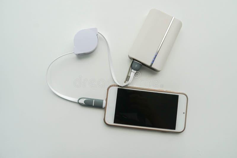 有电池充电的Solated白色智能手机从便携式的力量银行 免版税库存照片