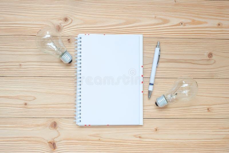 有电灯泡和被粉碎的纸的空白的笔记本在木桌、顶视图和拷贝空间上 想法,创造性,创新,解答,S 库存照片