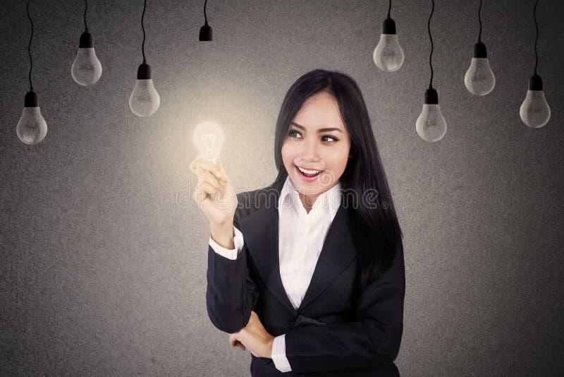 有电灯泡的女实业家 免版税库存图片