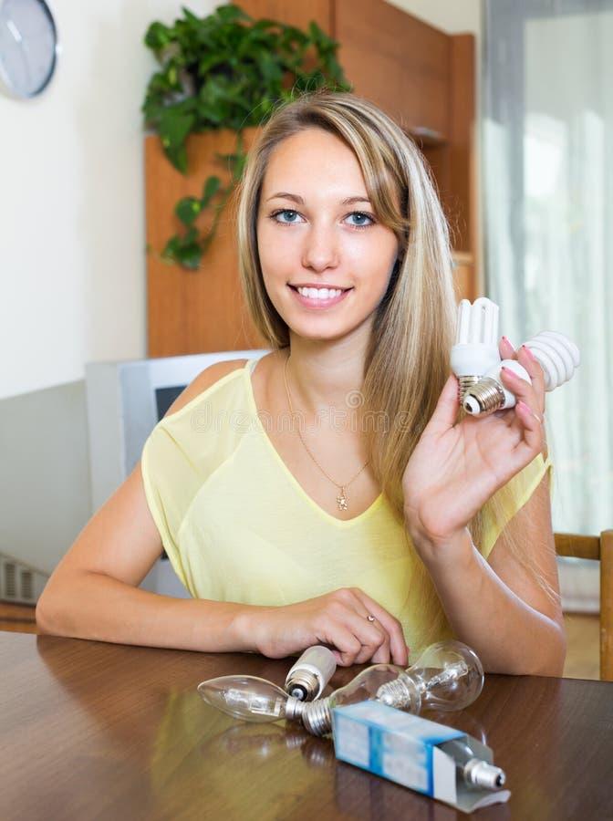 有电灯泡的妇女在家 免版税库存图片