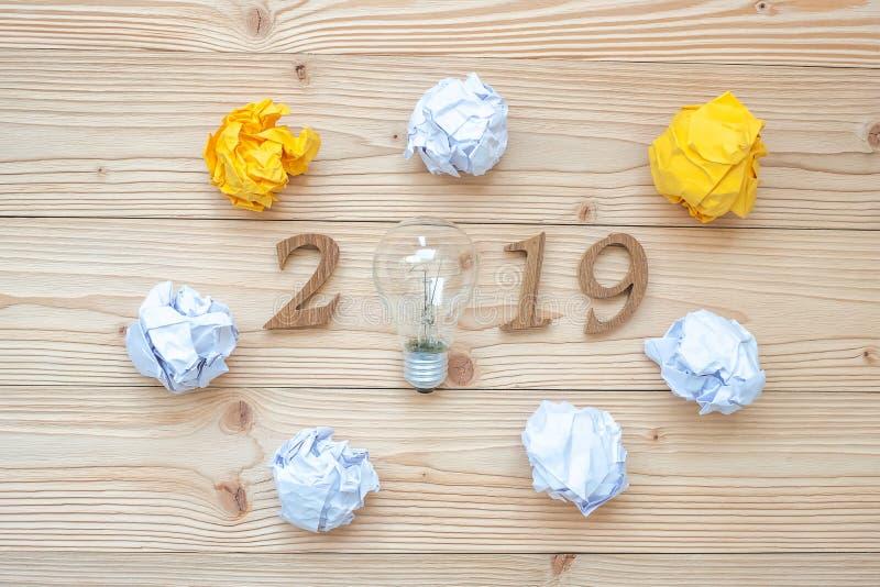 有电灯泡的2019新年快乐有被粉碎的纸的和在桌上的木数字 新的开始,想法,创造性,创新,Resolut 图库摄影