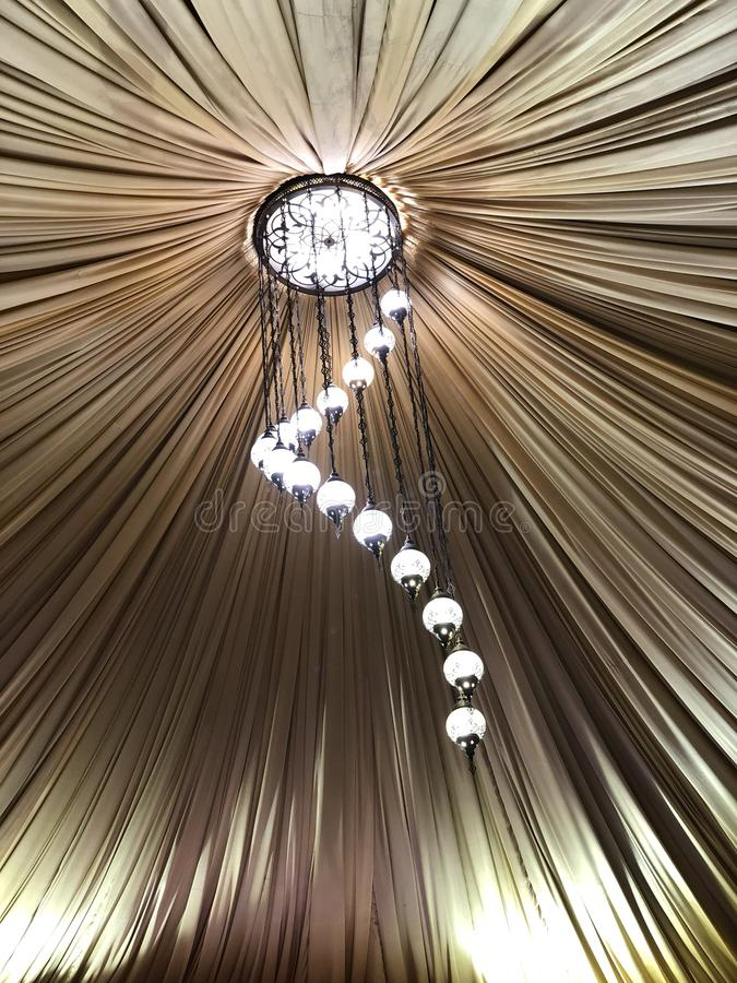 有电灯泡诗歌选的装饰的帐篷 婚礼设定了在大厦里面的白皮书灯笼,在布料屋顶装饰下 库存照片
