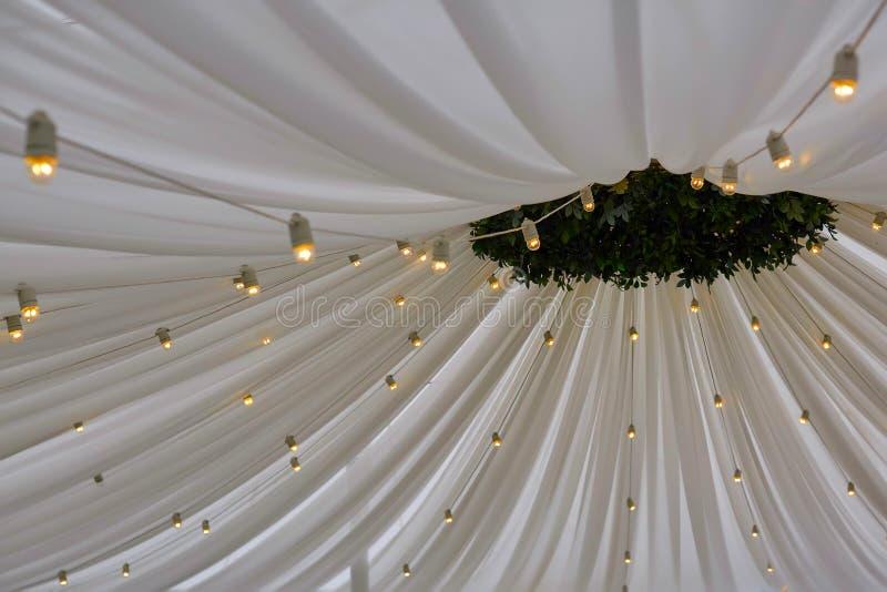 有电灯泡诗歌选的装饰的帐篷 婚礼设定了在大厦里面的白皮书灯笼,在木屋顶装饰下 库存照片