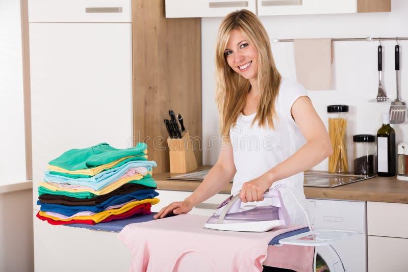 有电熨斗的微笑的妇女电烙的衣裳 免版税库存图片