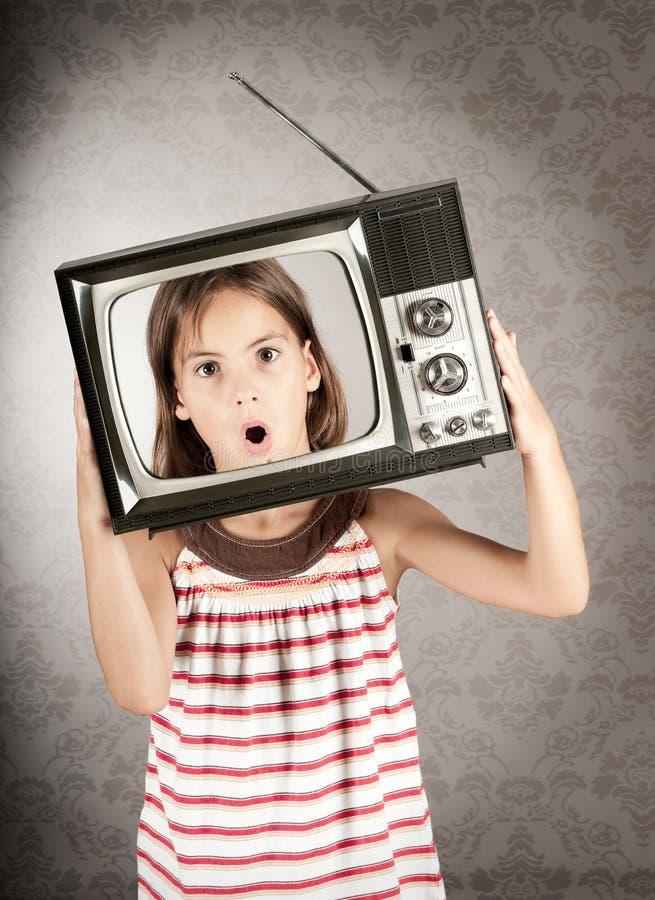 有电视的女孩在她的题头 库存图片