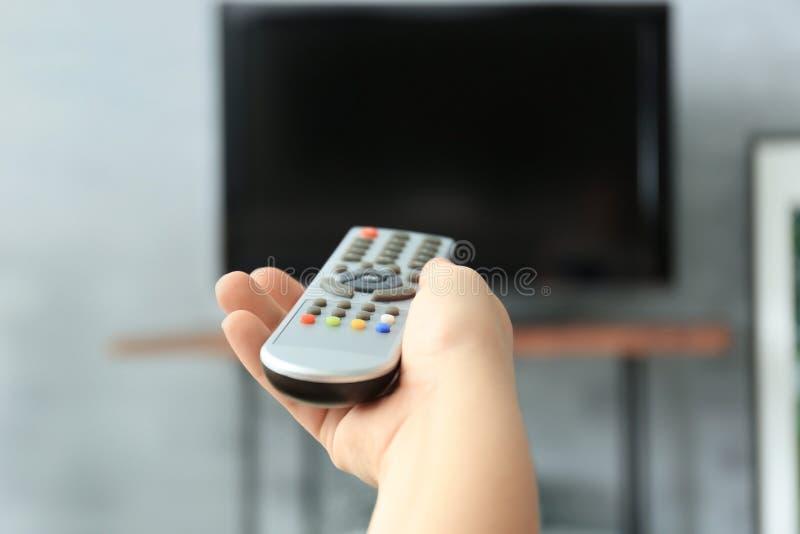 有电视遥控开关渠道的妇女 免版税库存照片