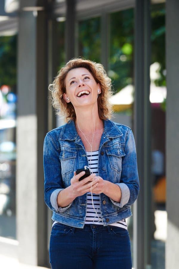 有电话和耳机的笑的妇女走在城市的 免版税库存照片