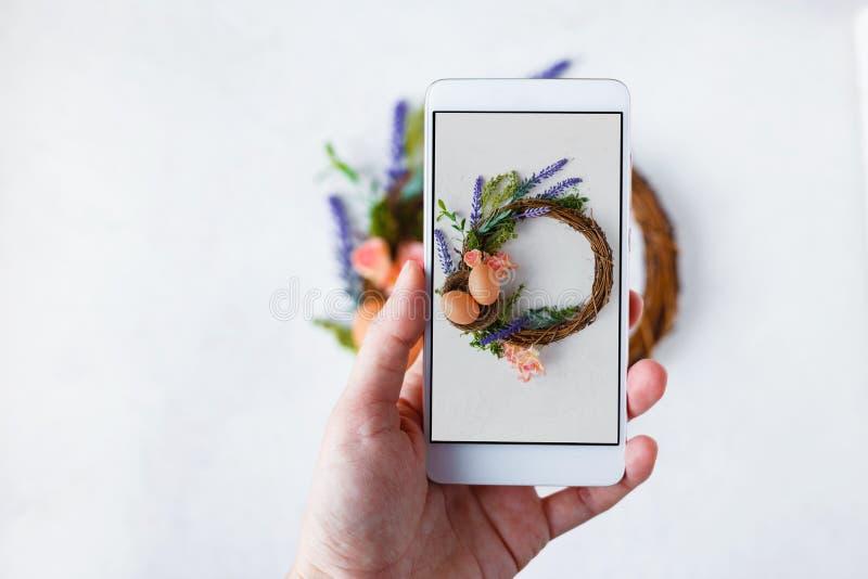 有电话照片复活节花圈的与明亮的春天花,巢女性手用复活节彩蛋 免版税图库摄影