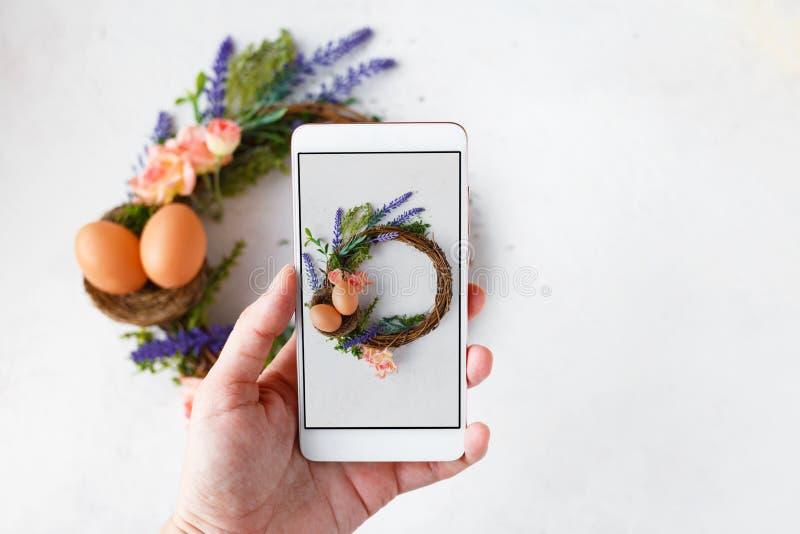 有电话照片复活节花圈的与明亮的春天花,巢女性手用复活节彩蛋 免版税库存照片
