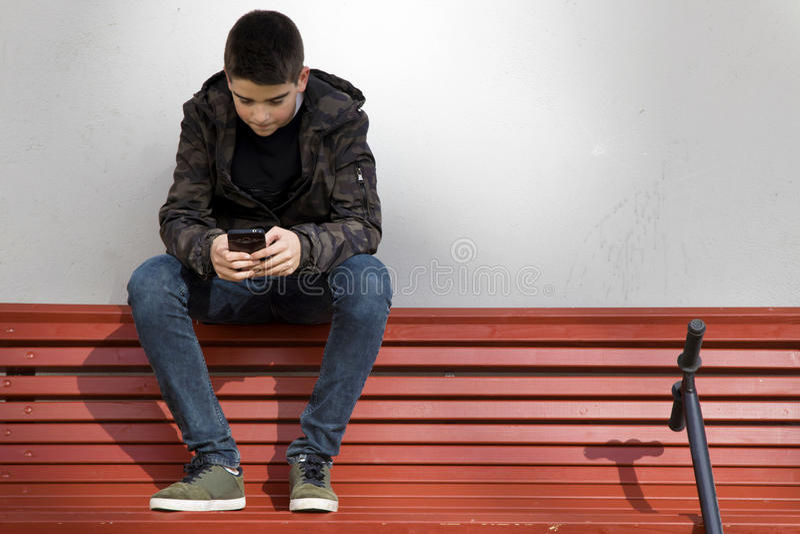 有电话电话的孩子在街道 免版税图库摄影