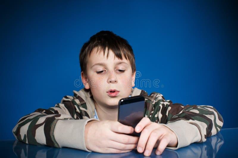 有电话的十几岁的男孩在手中 免版税库存图片
