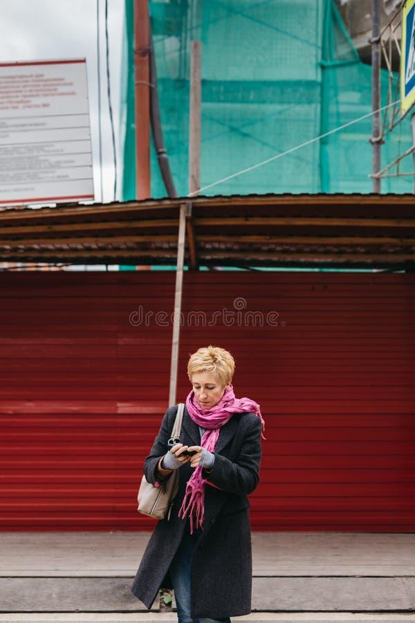 有电话的妇女在城市街道上 库存图片