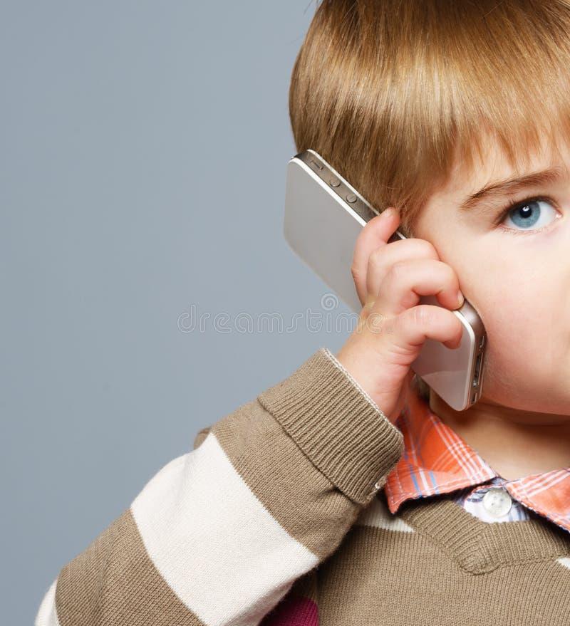 有电话的小男孩 免版税库存照片