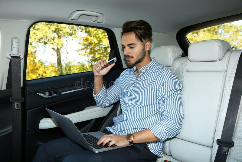 有电话的年轻帅哥使用膝上型计算机 免版税图库摄影