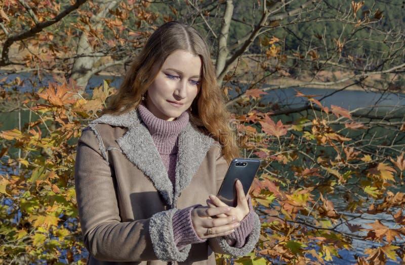 有电话的年轻美女在手上 免版税库存照片