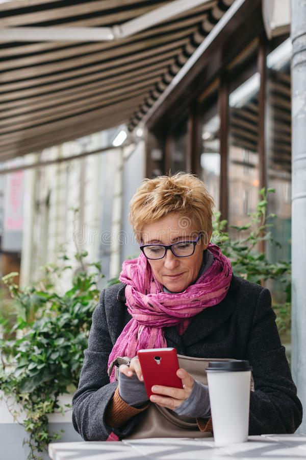有电话的微笑的妇女在咖啡馆 库存图片