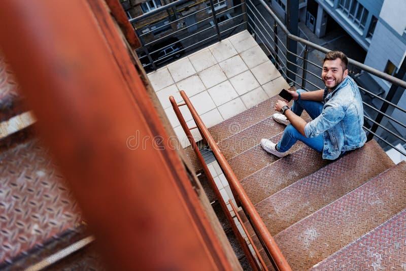 有电话的快乐的人在楼梯 库存照片