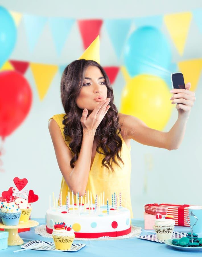 有电话的美丽的妇女在党,送亲吻 库存图片