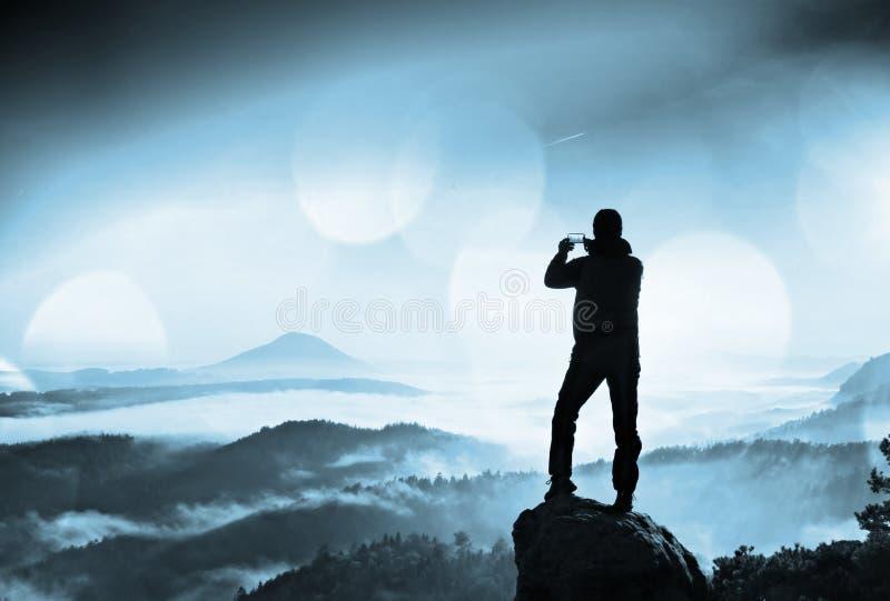 有电话的高背包徒步旅行者在手中做selfie 在山的晴朗的春天破晓 免版税库存照片